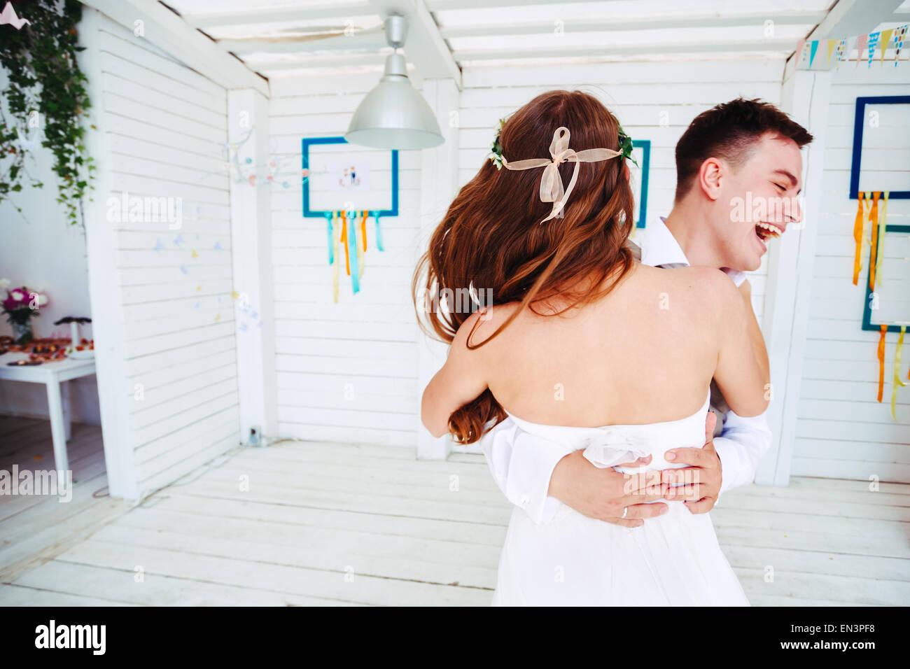 Felice giovani sposi, ridendo e ballando. Messa a fuoco selettiva in sposa. Foto Stock