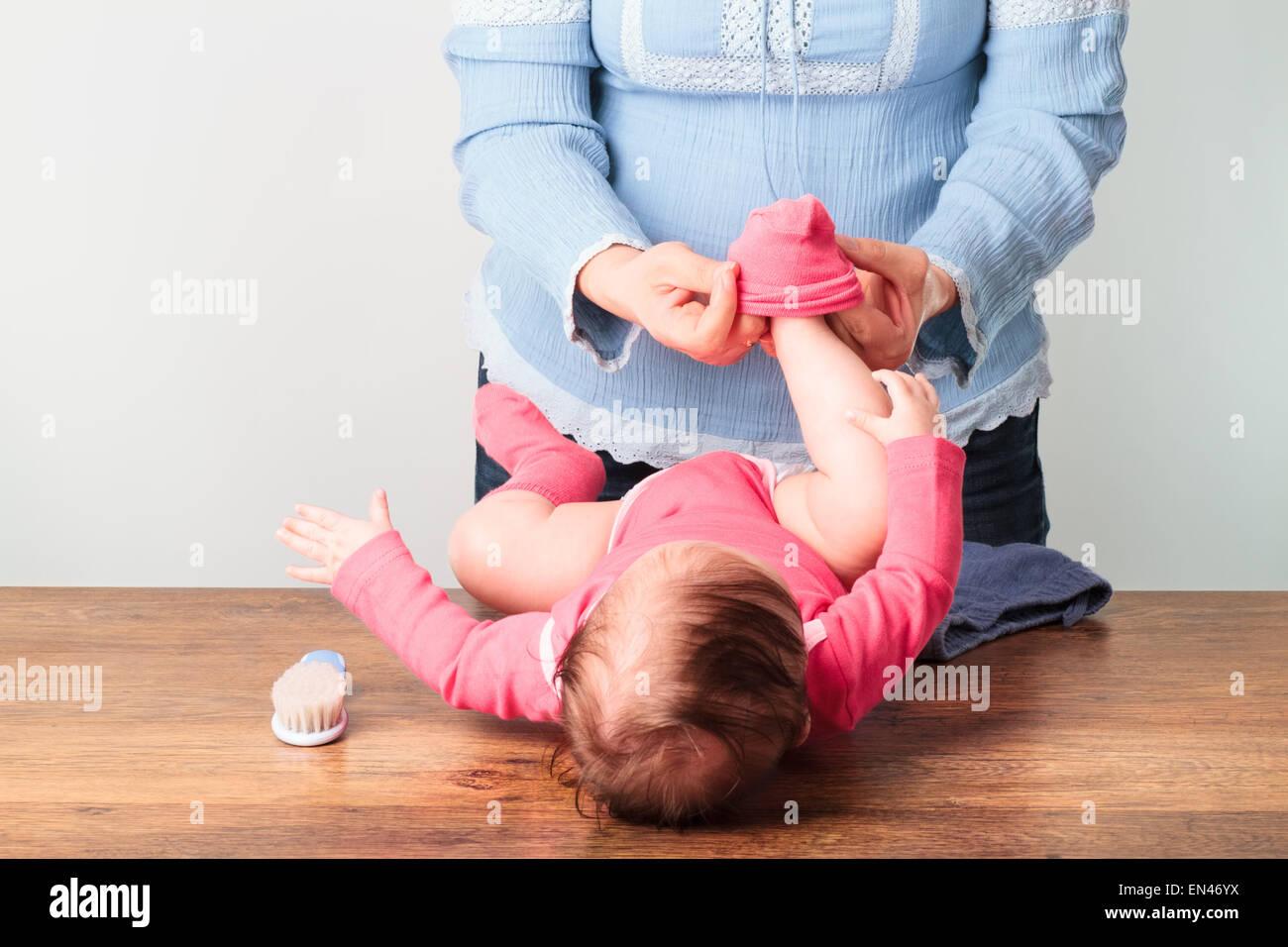 La mamma a mettere su i calzini la sua piccola bambina Immagini Stock
