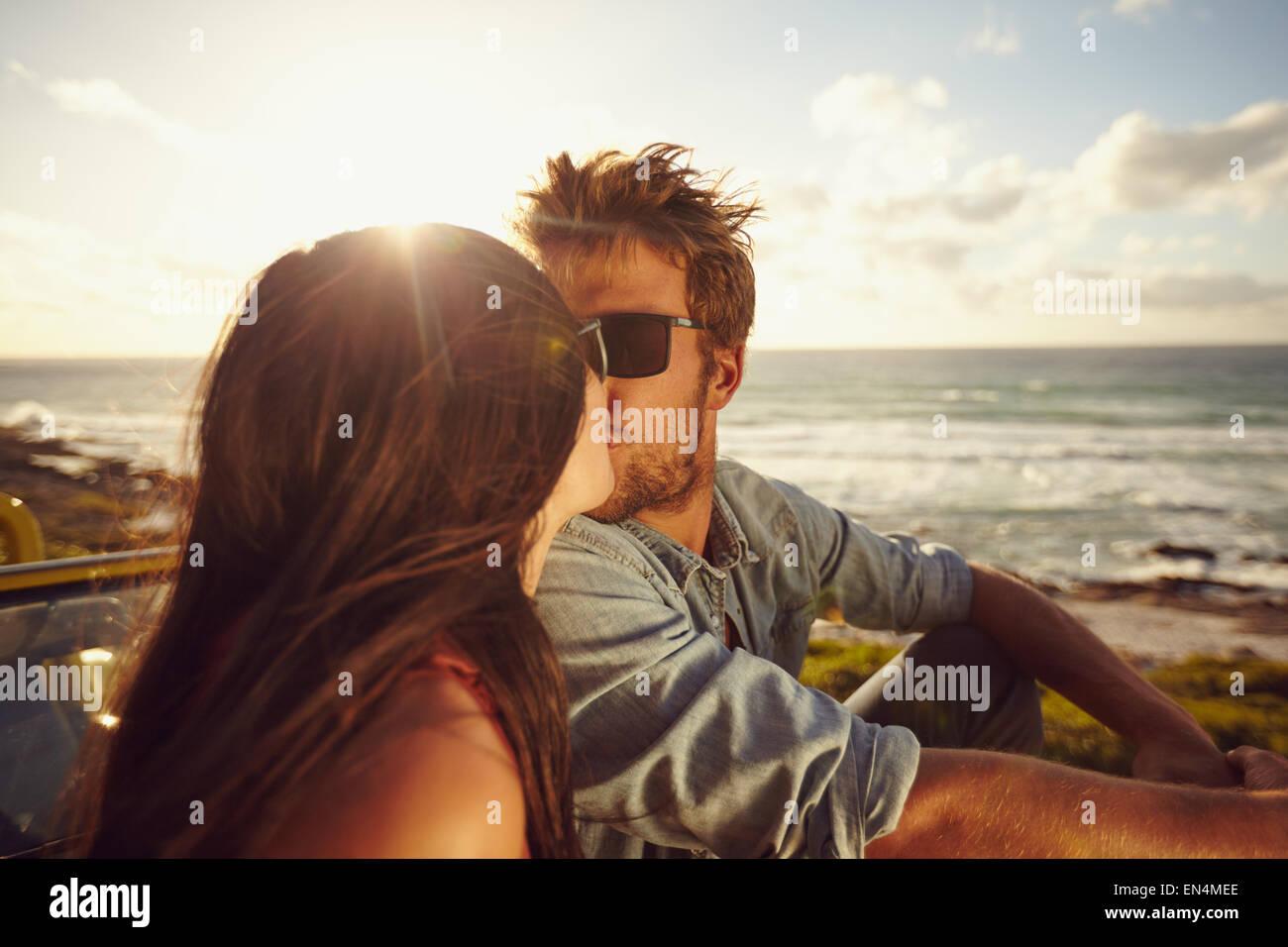 Affettuosa coppia giovane baciare sulla spiaggia. Amare giovane coppia con mare in background. Coppia romantica in vacanza. Foto Stock