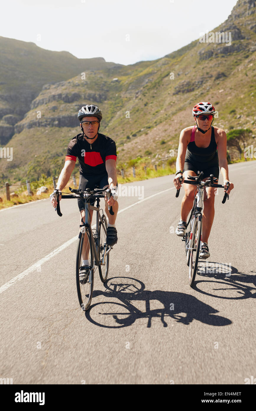 Paio di ciclisti in bicicletta sulla strada di un paese. Montare i giovani in bicicletta giù per la collina. Immagini Stock