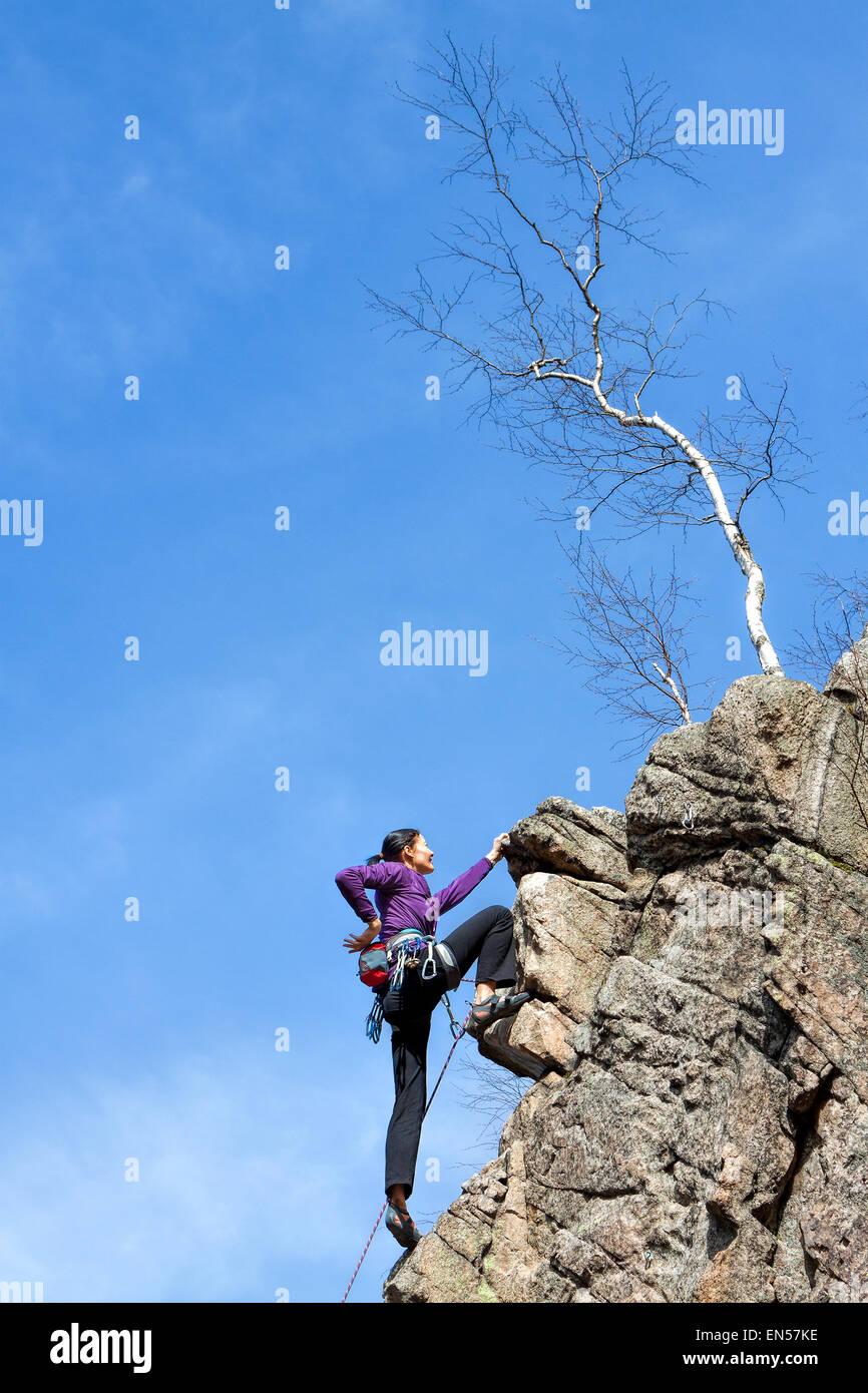 Felice femmina rocciatore su una ripida scogliera. Immagini Stock