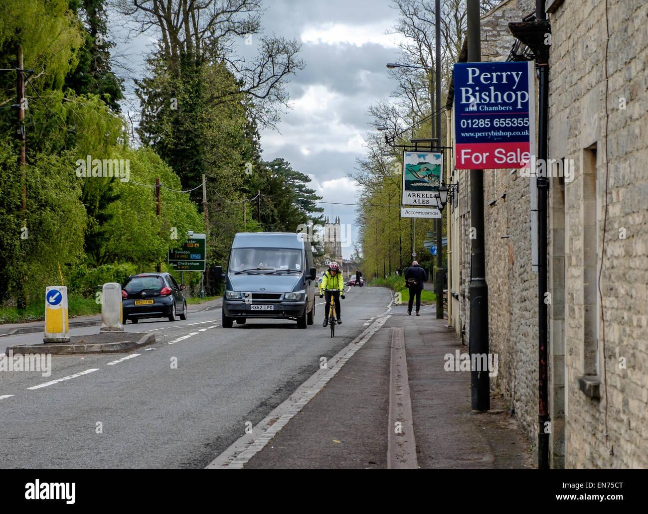Un van circa per sorpassare un ciclista in alta visibilità giacca hi-vis hi vis su una strada britannico Cirencester Immagini Stock