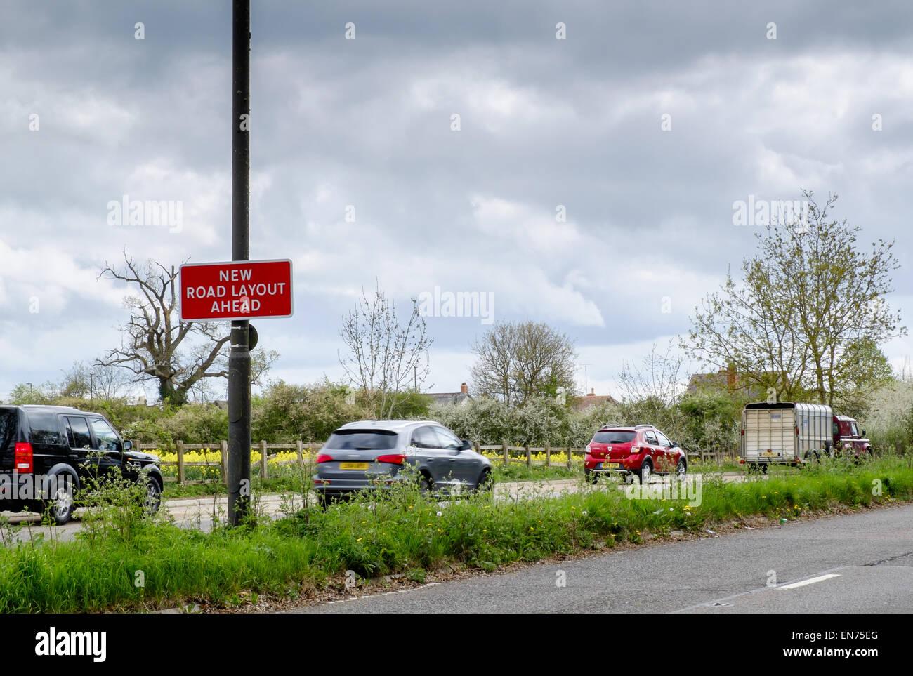 """Un """"nuovo tracciato stradale Ahead' segno su una strada principale in prossimità di un incrocio occupato Immagini Stock"""