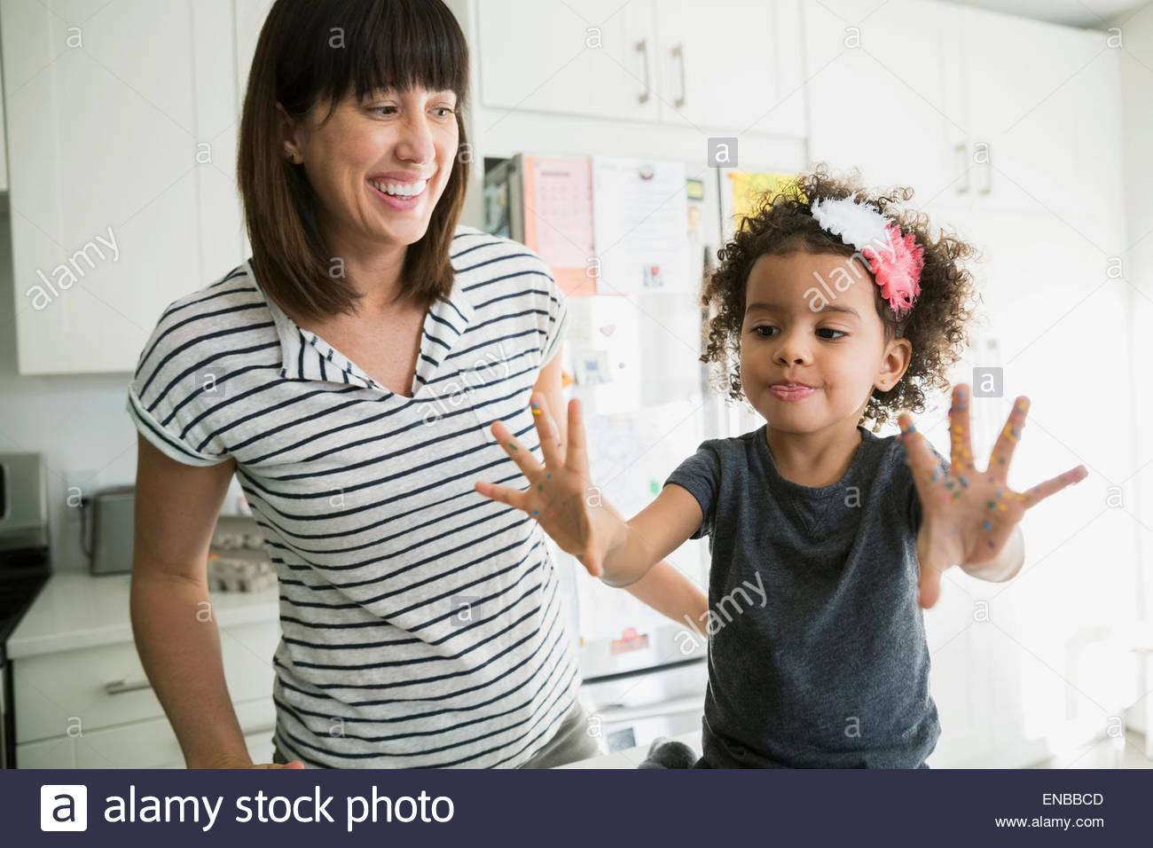 Madre guarda la figlia mostrano disordinato mani di cottura Immagini Stock