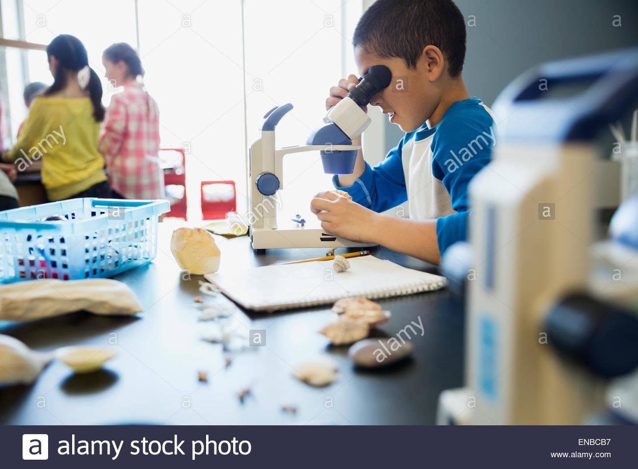 Scolaro usando microscopio nella scienza in aula di laboratorio Immagini Stock