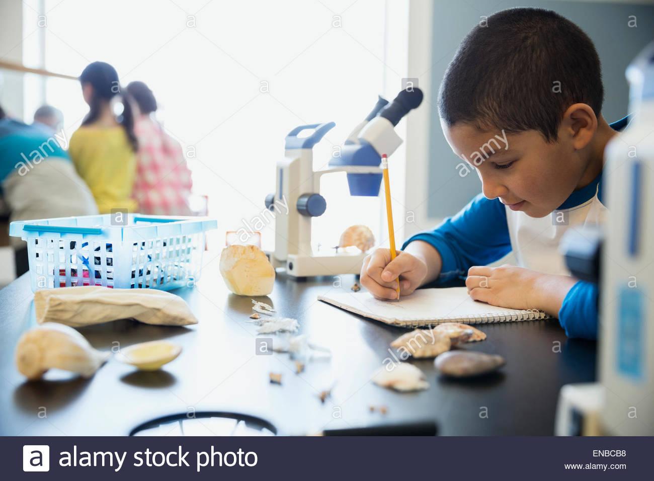 Scolaro prendere appunti al microscopio della scienza in aula di laboratorio Immagini Stock