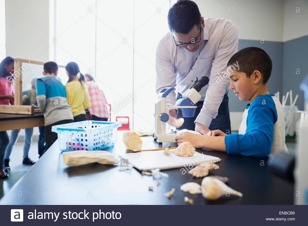 Maestro e scolaro al microscopio della scienza in aula di laboratorio Immagini Stock