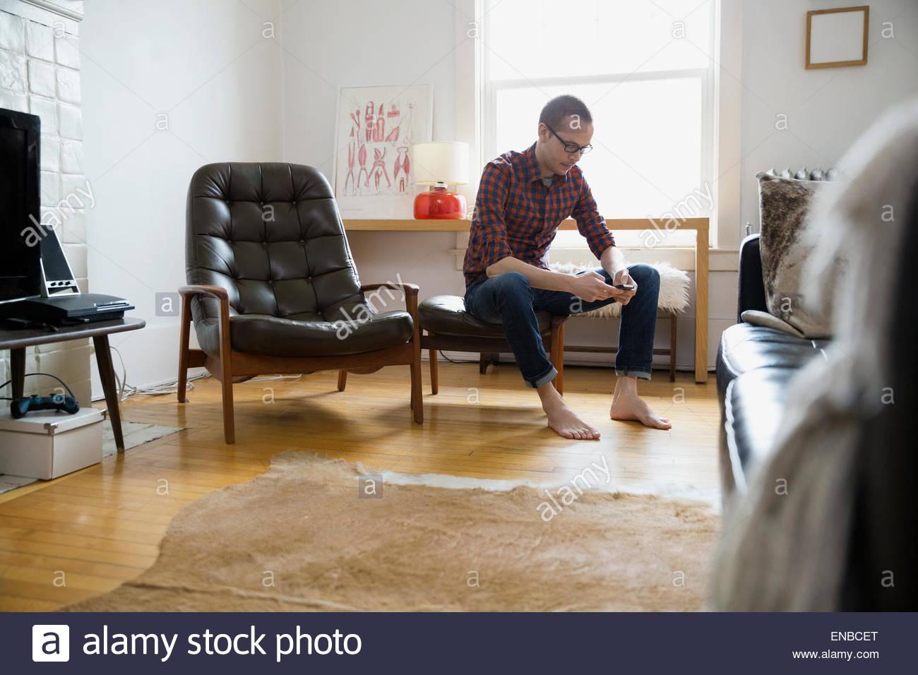 A piedi nudi uomo texting con telefono cellulare soggiorno Immagini Stock