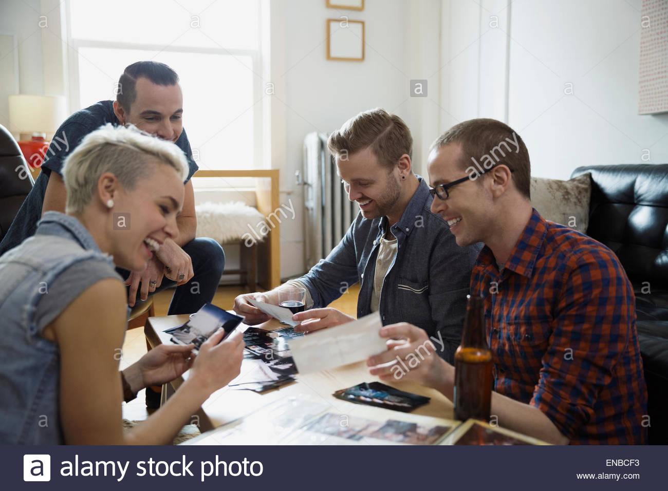 Amici guardando le fotografie di bere birra soggiorno Immagini Stock