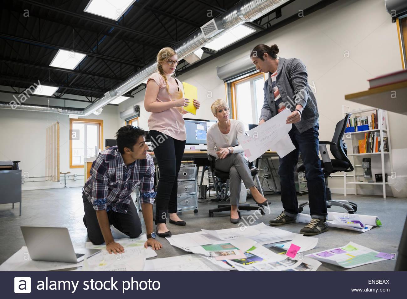 Graphic Designer incontro rivedendo le prove su pavimento per ufficio Immagini Stock