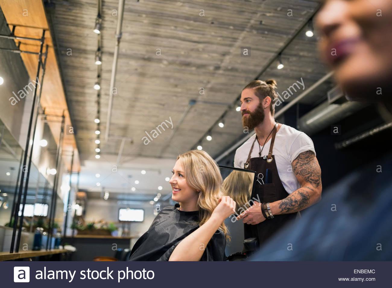 Un parrucchiere che mostra una donna con capelli specchio parrucchiere Immagini Stock