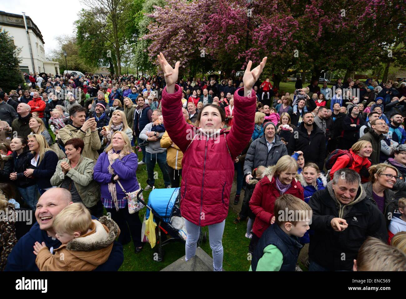 Rotherham, Regno Unito. Il 2 maggio 2015. Una giovane ragazza sperando di prendere un pezzo di pane che è gettato dalla torre della chiesa a Wath Tutti i Santi Chiesa Parrocchiale vicino a Rotherham, South Yorkshire. Un centinaio di pane bun sono gettati alla folla in attesa di seguito come parte dell'annuale Festival di Wath. Immagine: Scott Bairstow/Alamy Foto Stock