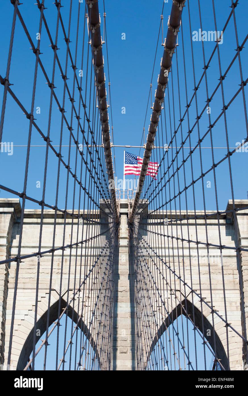 New York, nello Stato di New York, Stati Uniti d'America. Ponte di Brooklyn con la bandiera americana volare Immagini Stock