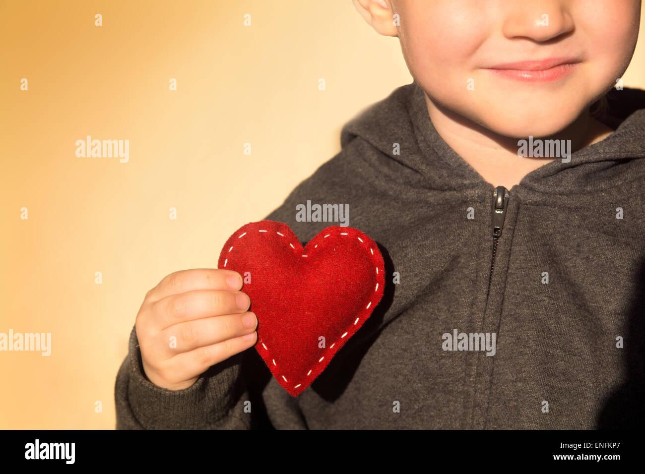 Cuore rosso nelle mani del bambino. Gentilezza concetto, dono fatto a mano e Valentino, close up, orizzontale, spazio Immagini Stock