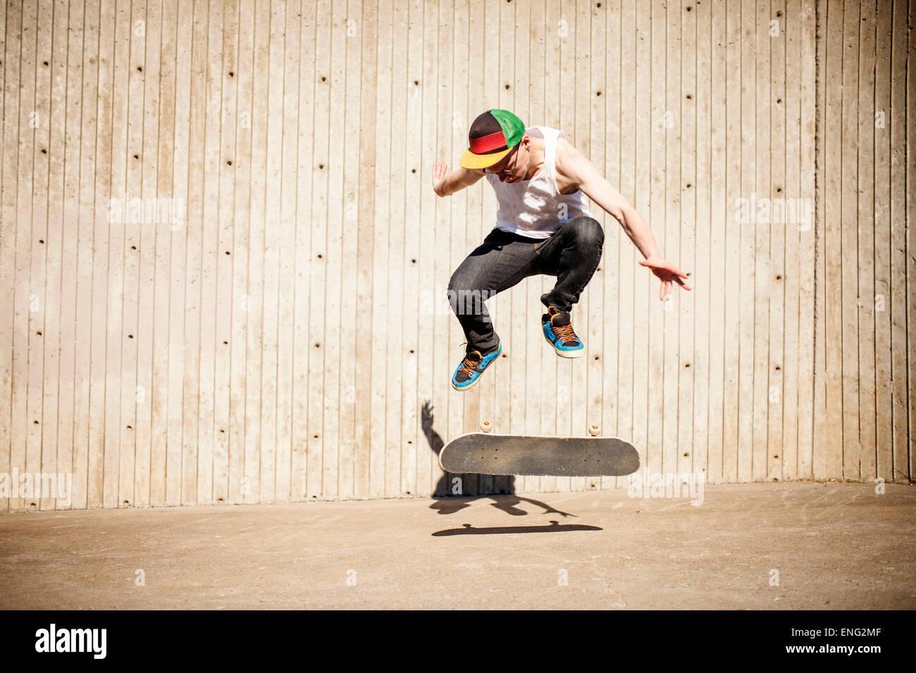 Uomo caucasico facendo skate trick vicino a parete in legno Immagini Stock