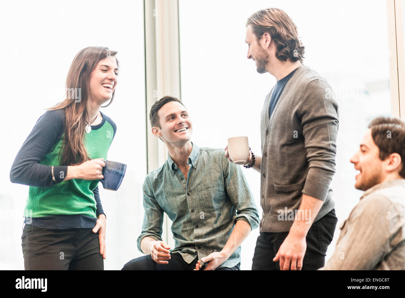 Quattro colleghi di lavoro su una pausa, ridere insieme. Immagini Stock