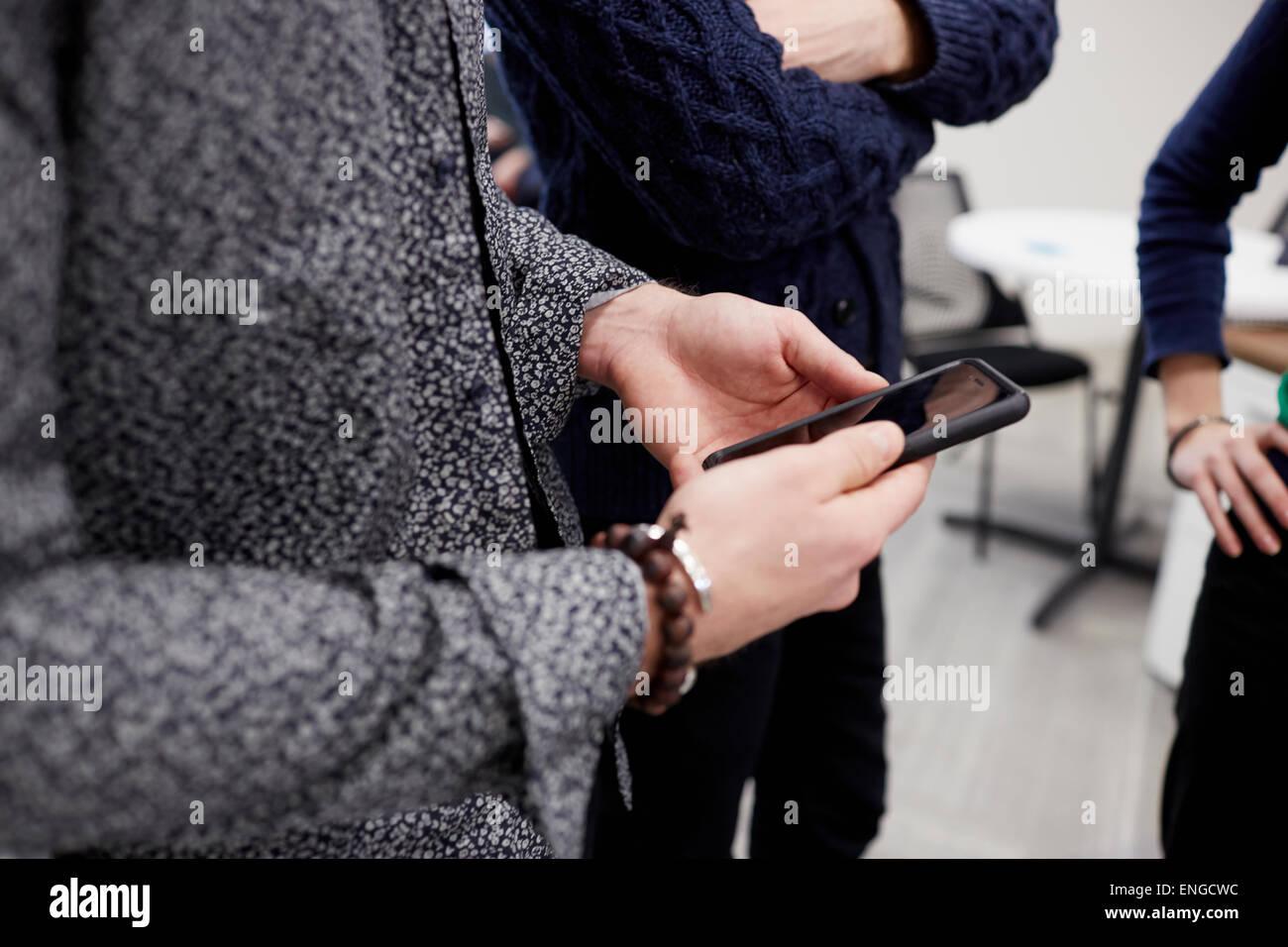 Tre persone in piedi in un ufficio, uno tenendo un telefono intelligente. Un incontro standup. Immagini Stock