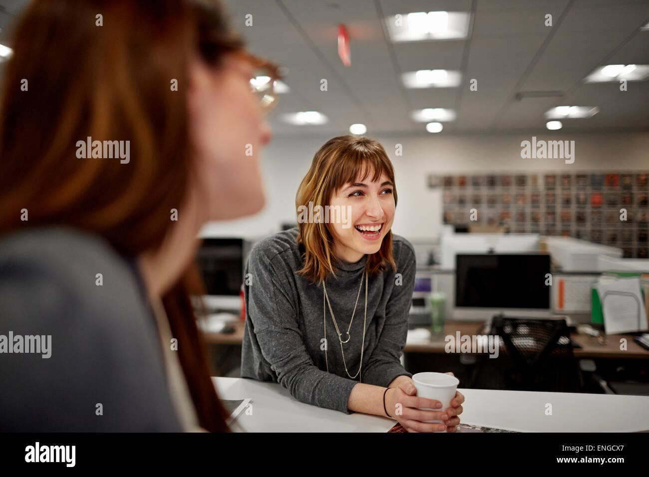 Due donne seduti in un ufficio a parlare. Immagini Stock