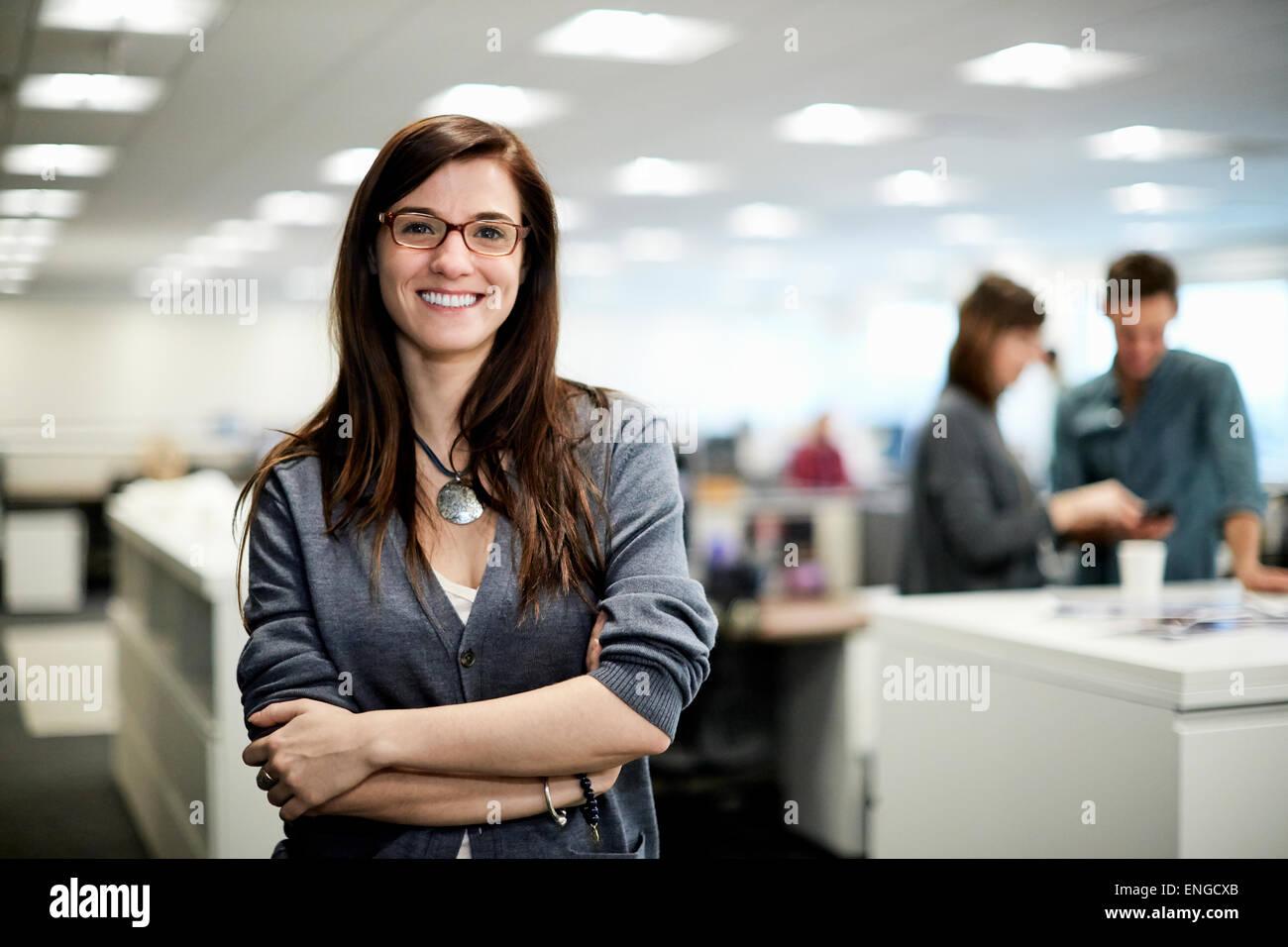 Una donna con i bracci ripiegati sorridente. Foto Stock