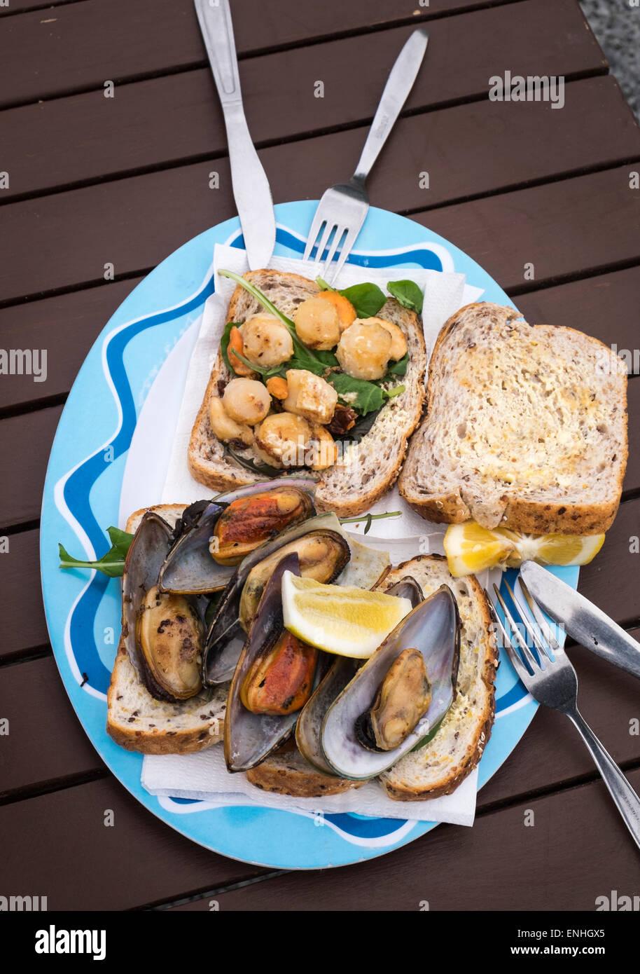 Capesante alla griglia e verde cozze a labbro sul pane in un cibo all'aperto shack sulla spiaggia di Kaikoura, Nuova Zelanda Foto Stock