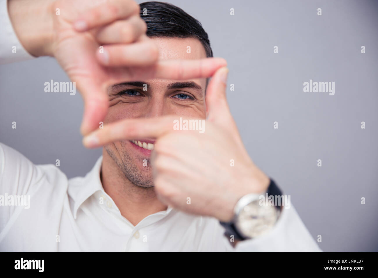 Imprenditore rendendo il telaio con le dita su sfondo grigio e guardando la fotocamera Immagini Stock