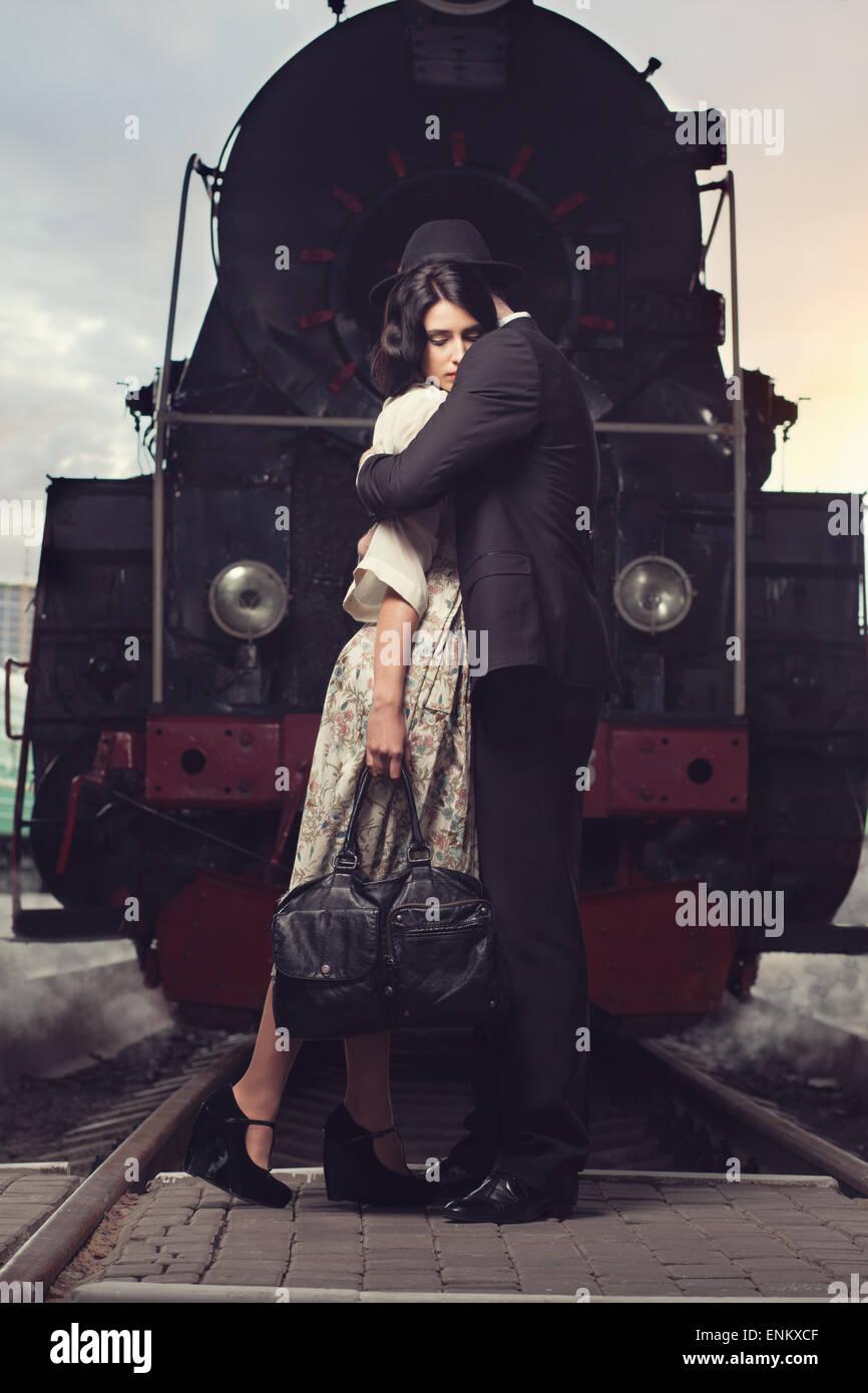 Il troncaggio della coppia adorabile sulla stazione ferroviaria a sfondo locomotore Immagini Stock