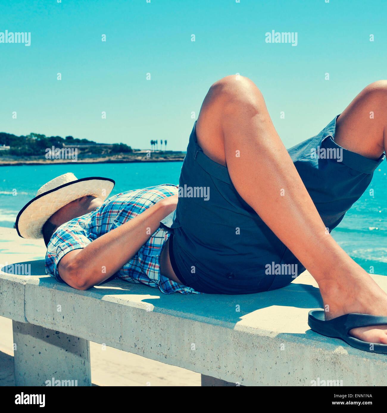 Un giovane uomo caucasico con un cappello di paglia sul suo volto disteso in un banco di strada vicino al mare Immagini Stock