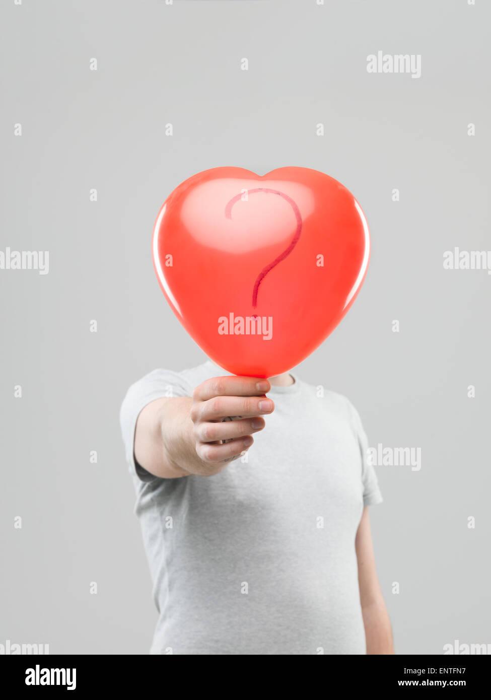 Uomo caucasico di contenimento a forma di cuore di ballon con punto interrogativo di fronte la sua testa contro Immagini Stock