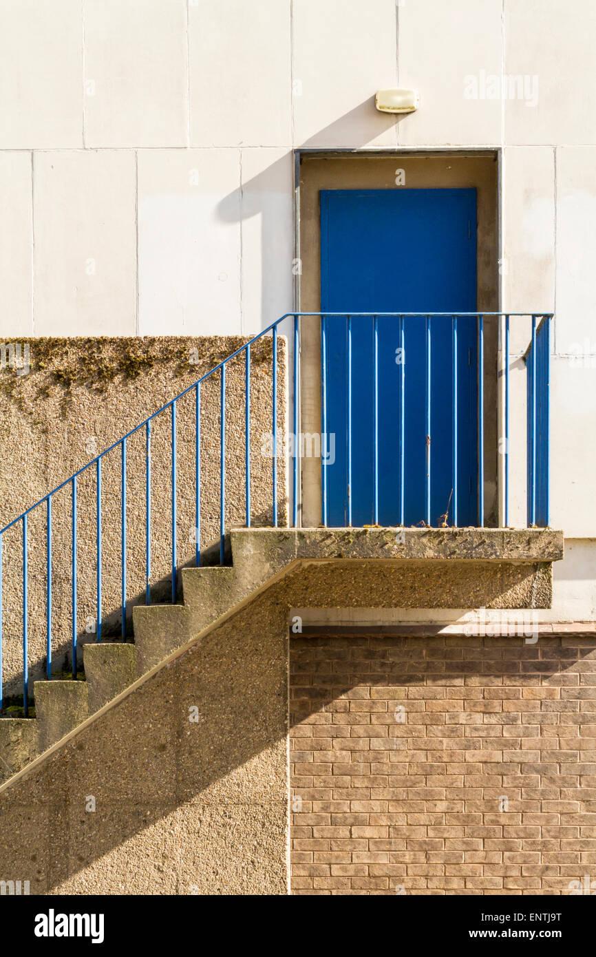 Passi con ringhiere che conduce fino a una porta blu sul retro di un edificio, England, Regno Unito Immagini Stock