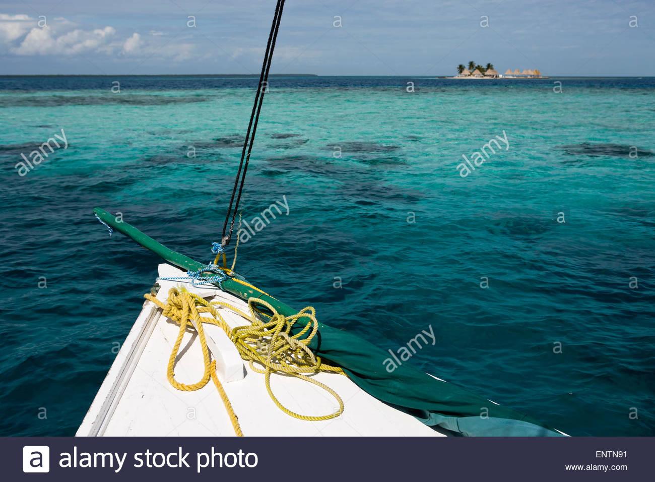 10b290dfa13648 La punta di una barca a vela e un piccolo atollo di Isola nel mare dei  Caraibi al largo delle coste del Belize.