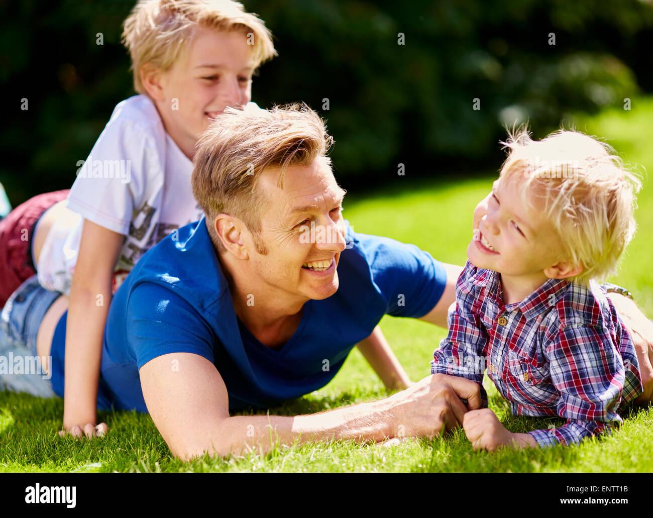 Padre a giocare con i bambini è all'aperto Immagini Stock