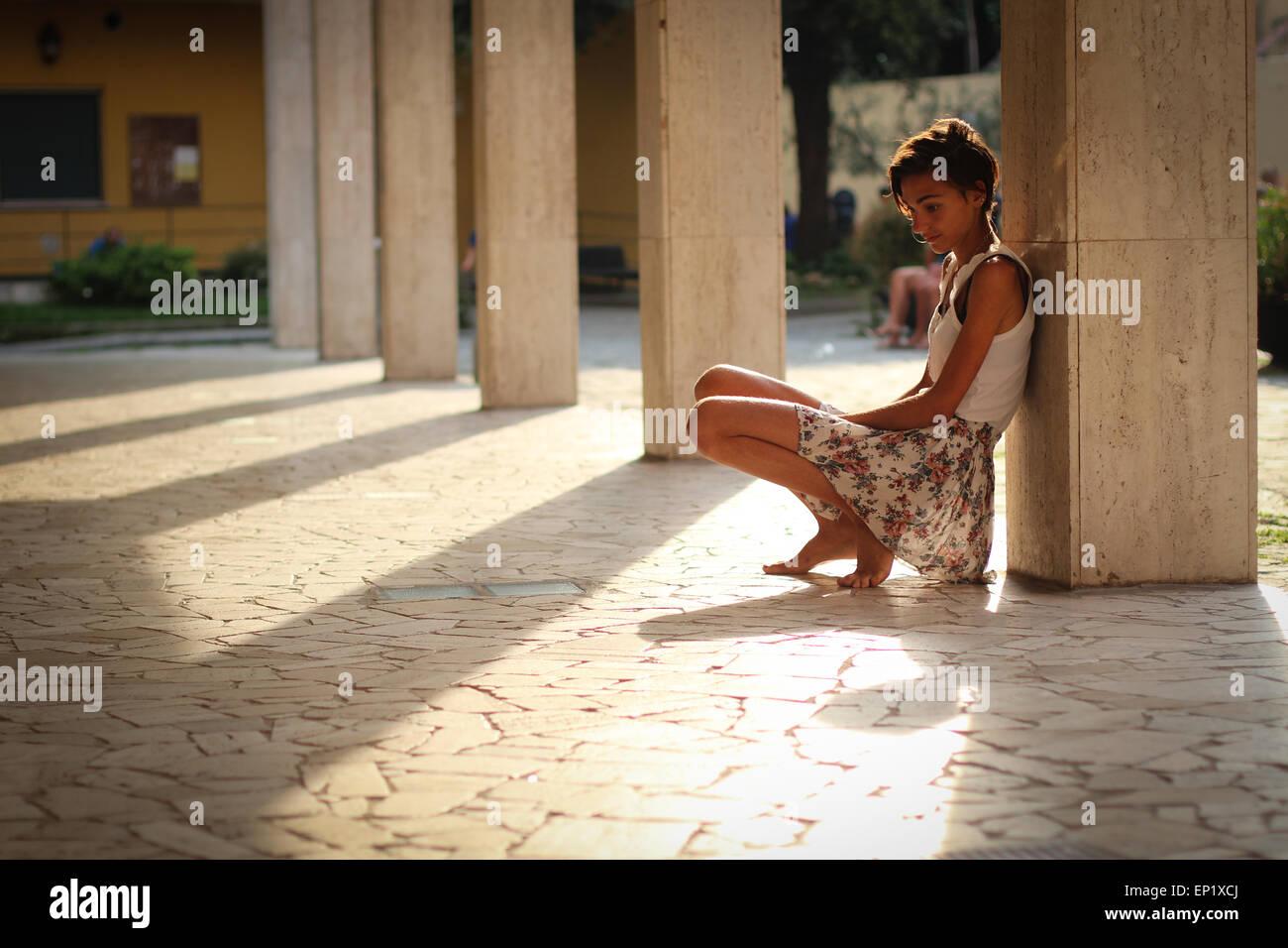 Ragazza appoggiata contro un pilastro in un cortile Foto Stock
