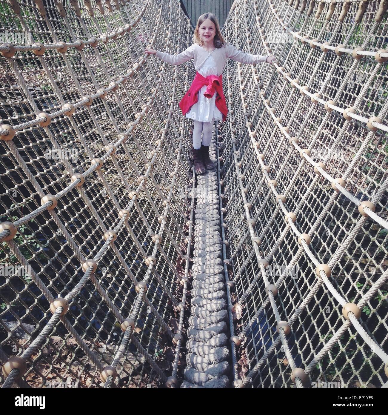 Ragazza in piedi su un ponte di corde Immagini Stock