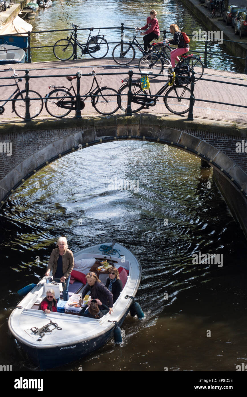 Amsterdam Reguliersgracht Canal con una piccola barca e turisti sul noleggio di biciclette aventi difficoltà escursioni Foto Stock
