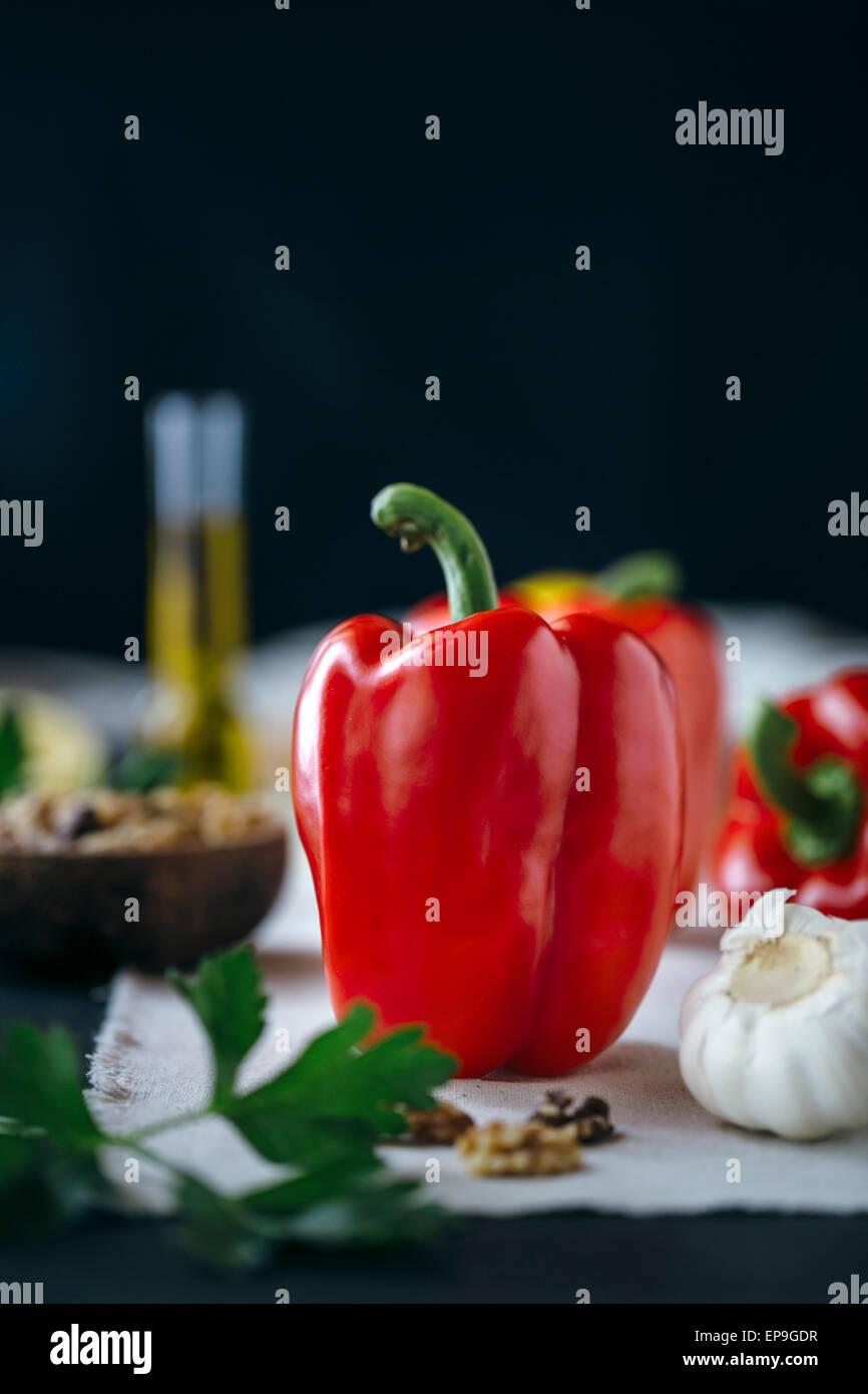 Ingredienti per arrosto di pepe rosso dip sono sul display e un peperone rosso è a fuoco. Immagini Stock