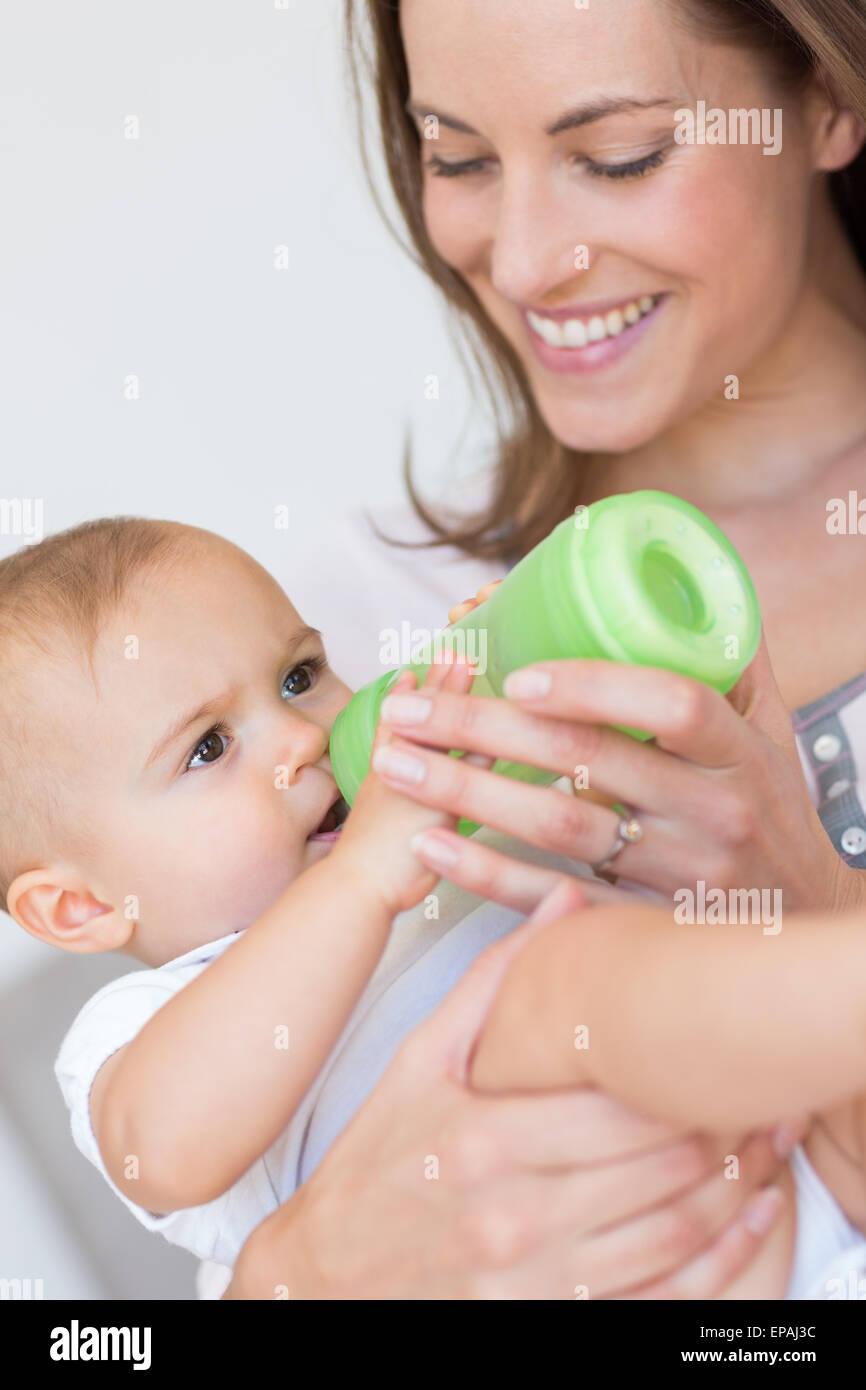 La madre del bambino di alimentazione con bottiglia di latte Immagini Stock