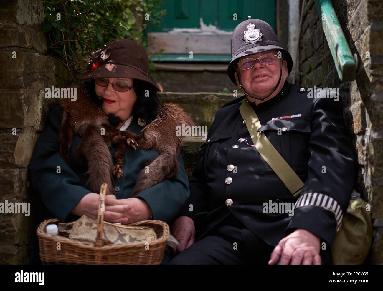 Jolly vecchio poliziotto e la moglie seduta in una rampa di scale Immagini Stock