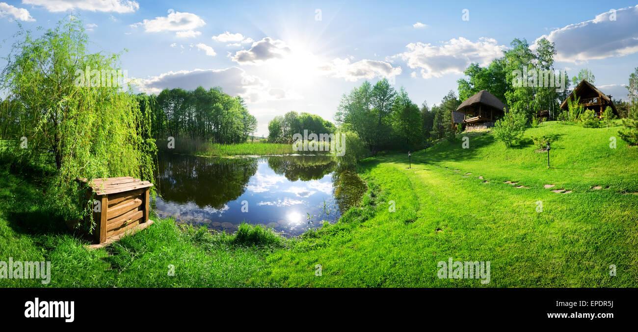 Casa in legno vicino al fiume e al giorno di sole Immagini Stock