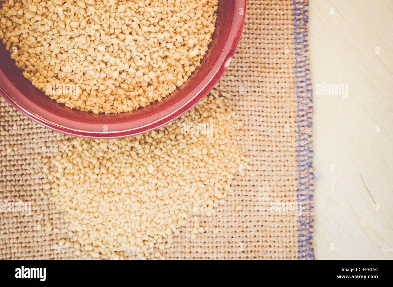 Il cous cous grani in un marrone vaso di porcellana su una superficie di tela Immagini Stock