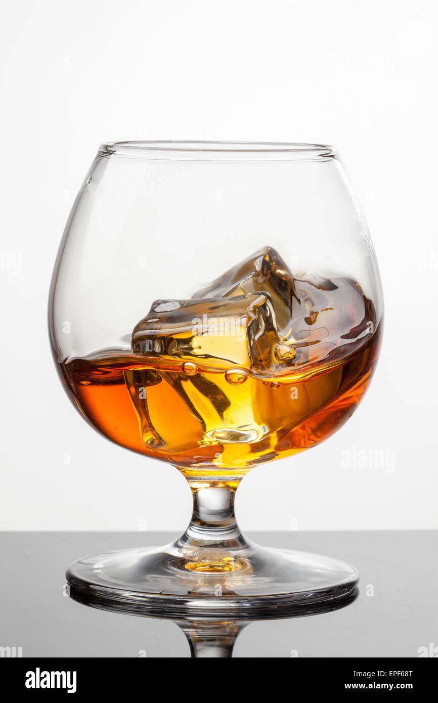 Splash di whiskey con ghiaccio in vetro isolato su sfondo bianco. Foto raw Immagini Stock