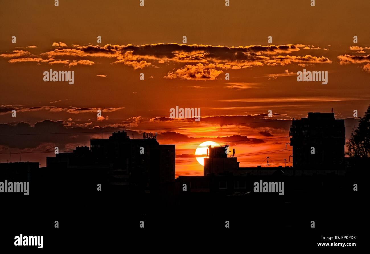 Silhouette di edifici in arancione tramonto, edifici sagome nel tramonto colorato, serata in città, drammatico tramonto Foto Stock