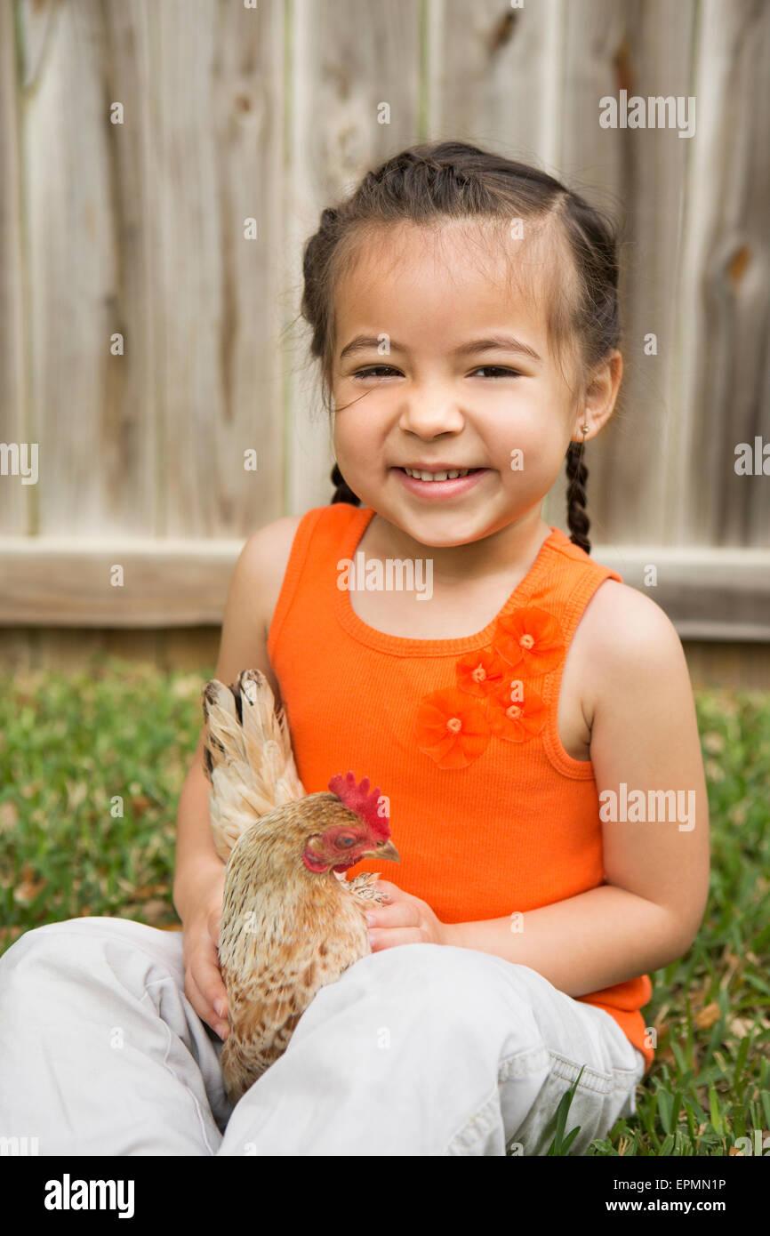 Una giovane ragazza con un pollo. Immagini Stock