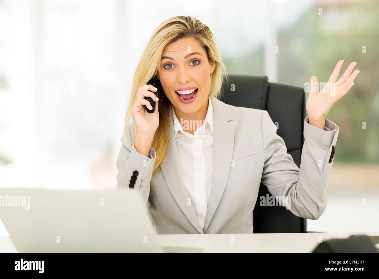 Felice imprenditrice ricevere notizie entusiasmanti per telefono Immagini Stock