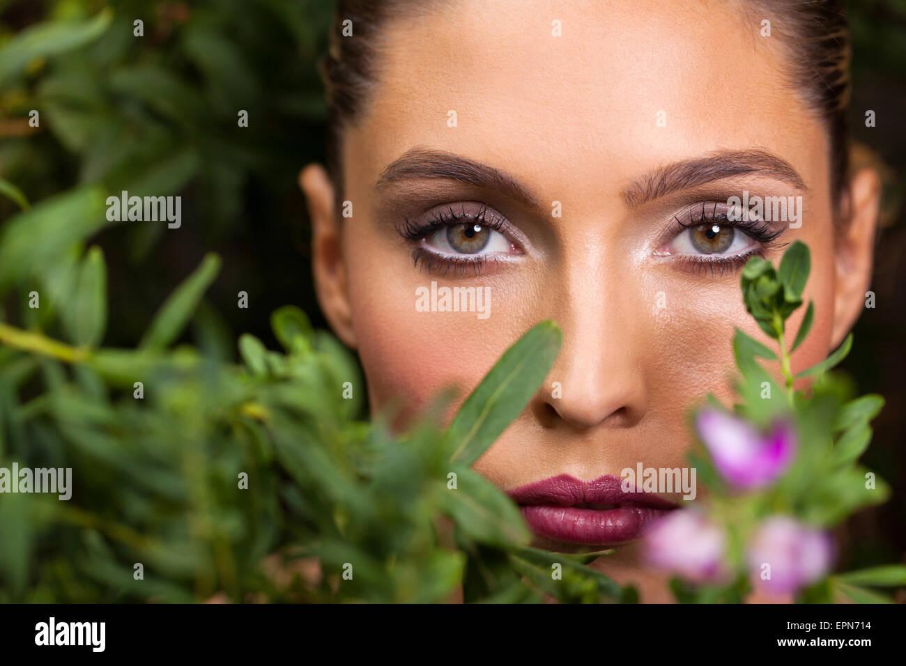 Bella giovane donna in posa tra il verde delle foglie Foto Stock
