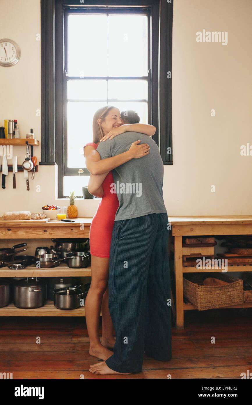 Piscina colpo di coppia giovane che abbraccia ogni altra in cucina. Lunghezza completa immagine di uomo abbracciando Immagini Stock