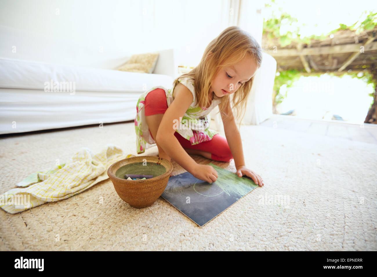 Colpo di piccoli innocenti caucasian ragazza seduta sul pavimento la colorazione di una foto con un colore chalks. Immagini Stock