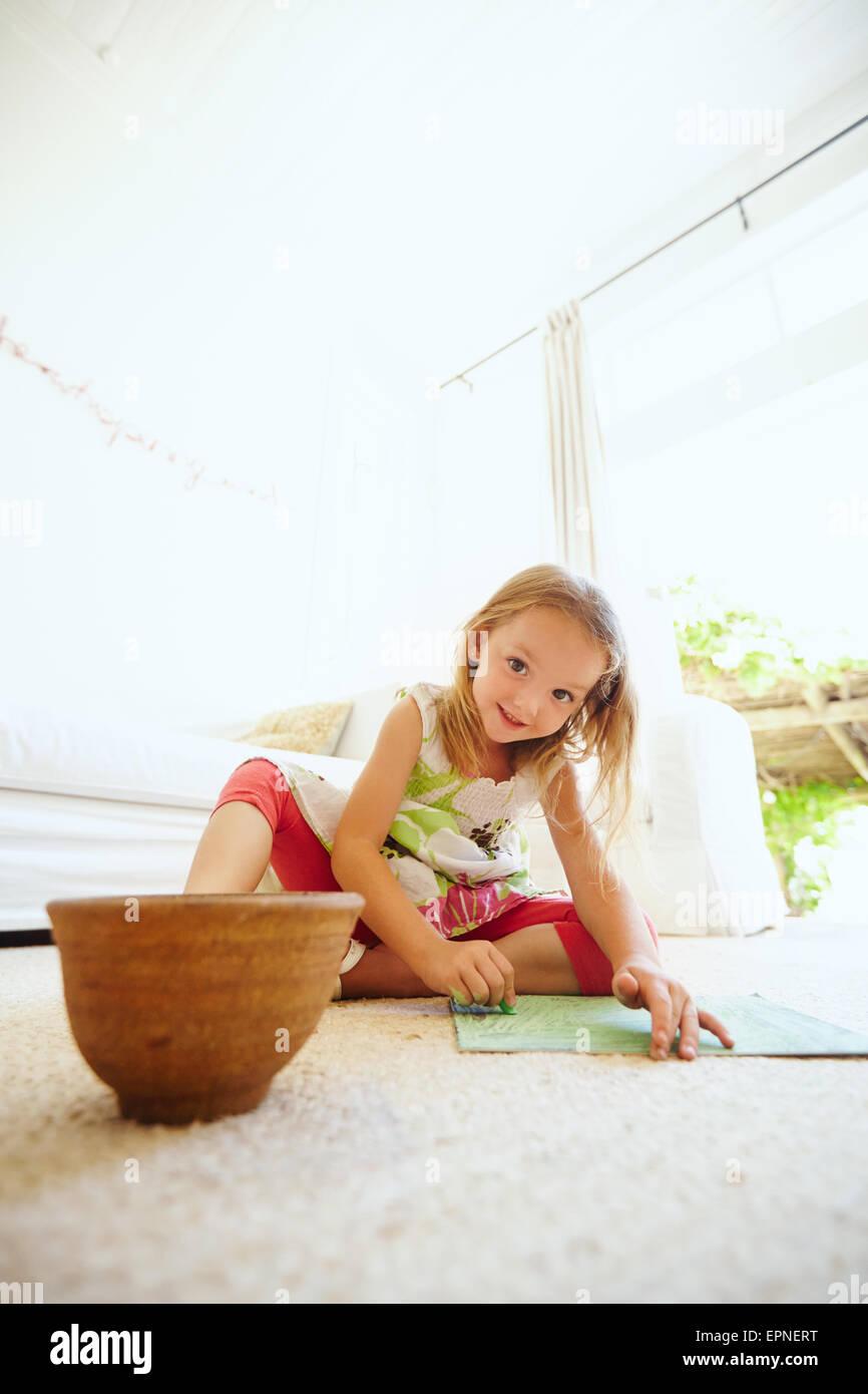 Ritratto di ragazza in età prescolare colorazione immagine sul pavimento nella sua casa. Giovane ragazza seduta Immagini Stock