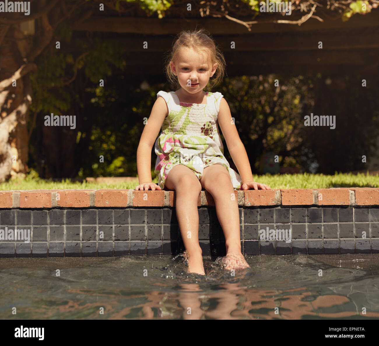Adorabile bambina godendo seduti a bordo della piscina sulla giornata di sole. Ragazza giovane con i suoi piedi Immagini Stock