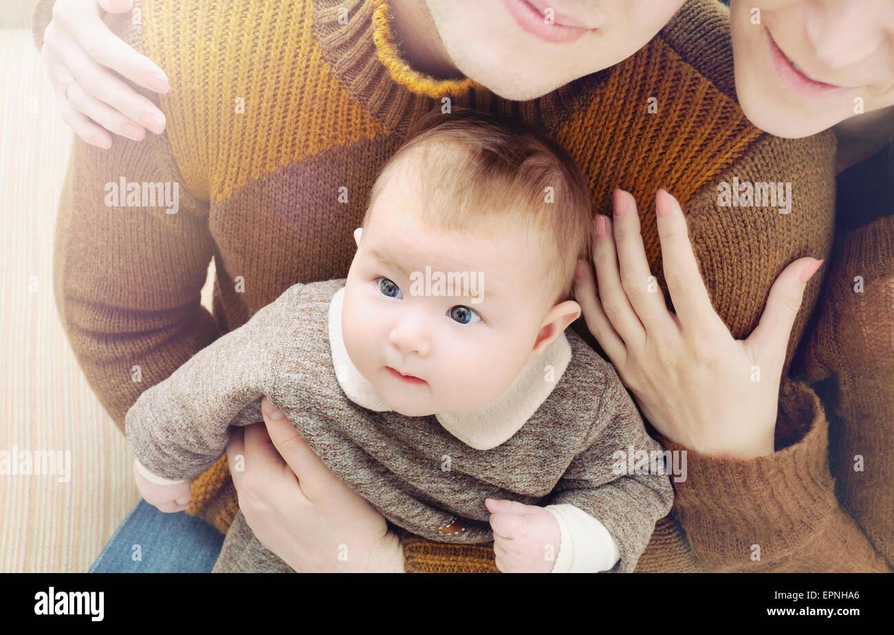La famiglia felice di tre, poco carino bambino con grandi occhi seduto sul genitore sulle sue ginocchia, il concetto Immagini Stock