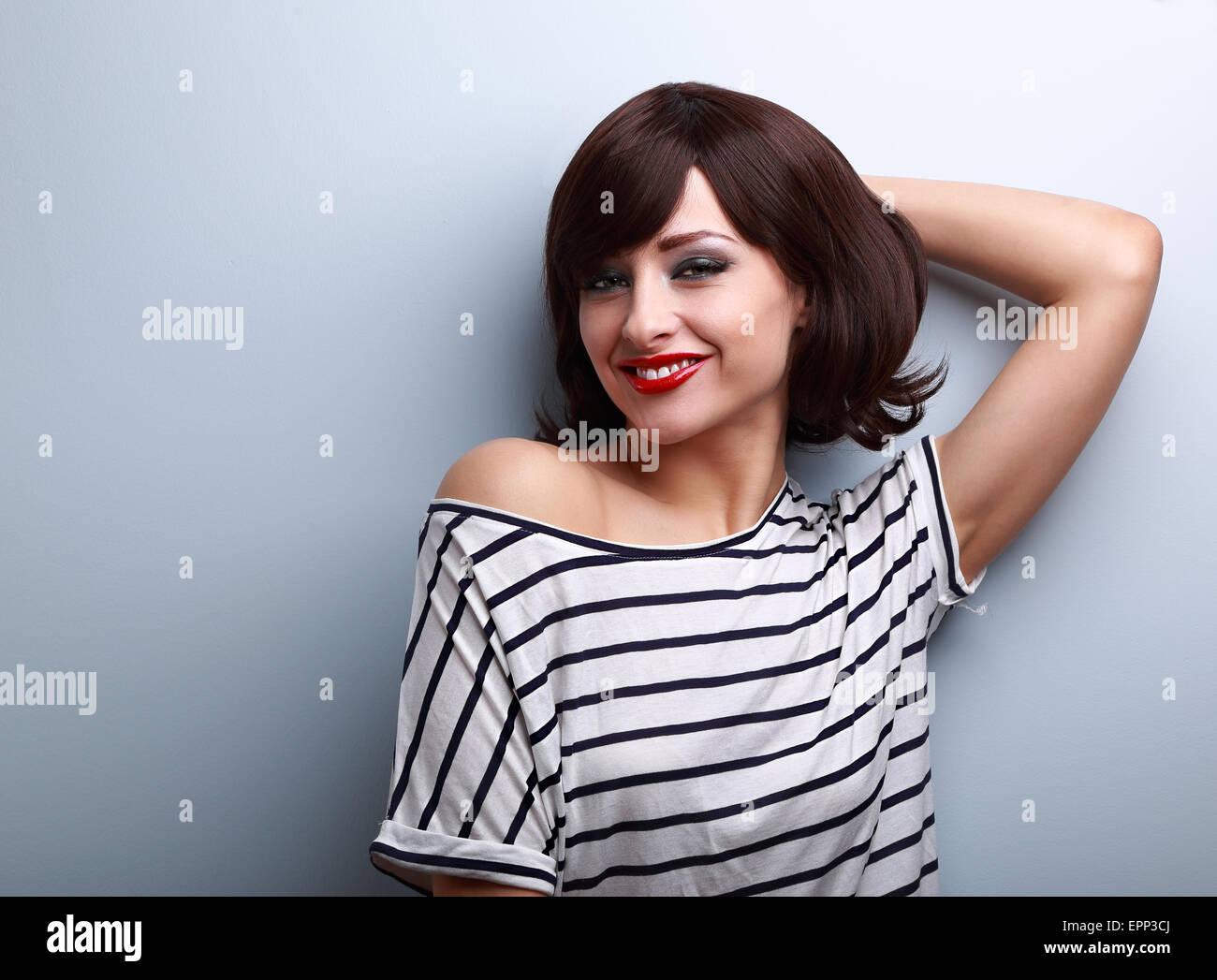 Sorridendo felice giovane donna in abbigliamento casual rilassante sulla parete blu sullo sfondo Immagini Stock
